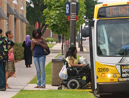 Black women including one using a wheelchair entering a bus