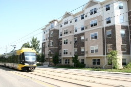 Light rail train in front of 5-story apartment building