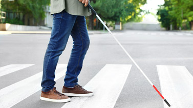 Visually impaired pedestrian using a white can to cross a street at a marked crosswalk