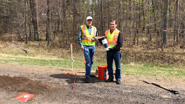 Researchers in the field holding runoff collection device