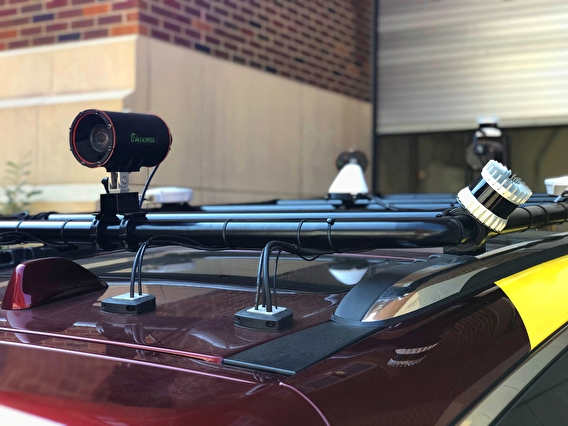 LiDAR units, cameras, and GPS antennas are affixed to the vehicle's roof rack.