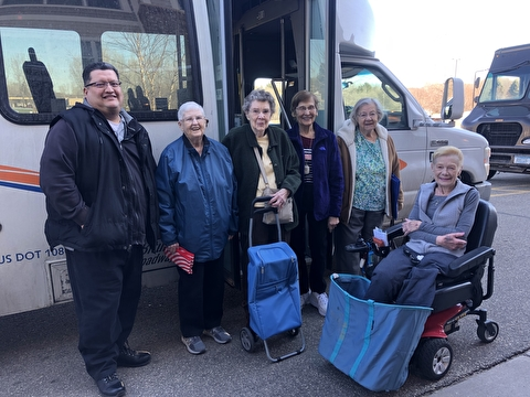 Older adults, including one in a wheelchair, outside a transit bus