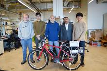 Five male researchers standing behind red bike in lab