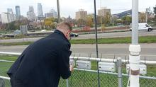 man measuring air quality next to highway