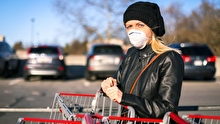Woman wearing a medical mask while pushing a cart in a parking lot